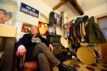 Christophe Calpini en interview durant le Cully Jazz, installé dans un canapé du tHBBC (Cully) sous un panneau de la Rue de Saint-Nicolas. Derrière, une grosse caisse et un porte-manteau. Plusieurs photos de Mehdi Benkler accrochées au mur.